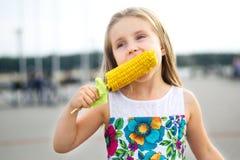 Entzückendes lustiges Mädchen, das Maiskörner am sonnigen Sommertag isst stockfotografie