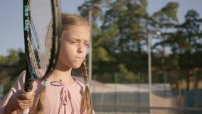 Entzückendes lustiges Mädchen des Porträts mit zwei Zöpfen, die draußen Tennis spielen Starkes Kind, das einen Schläger und einen stock footage