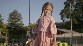 Entzückendes lustiges Mädchen mit zwei Zöpfen, die draußen Tennis spielen Starkes Kind, das ungefähr einen Schläger und einen Bal stock footage