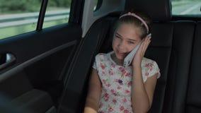 Entzückendes Mädchen, das auf Mobiltelefon im Luxusauto spricht stock footage