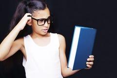 Entzückendes Mädchen, das in der Hand mit Brillen und Buch studiert Lizenzfreies Stockbild