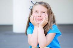 Entzückendes Mädchen, das draußen an Zukunft und Geschenke träumt und denkt lizenzfreie stockfotografie