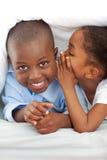 Entzückendes Mädchen, das etwas zu ihrem Bruder flüstert stockbilder