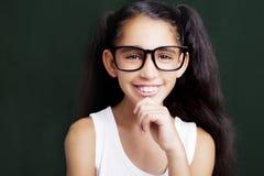 Entzückendes Mädchen, das mit Brillen auf dunklem Hintergrund studiert Lizenzfreies Stockbild