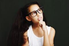 Entzückendes Mädchen, das mit Brillen auf schwarzem Hintergrund studiert Lizenzfreies Stockbild
