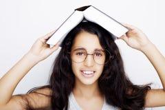 Entzückendes Mädchen, das mit Brillen und Buch auf dem Kopf studiert Lizenzfreies Stockfoto