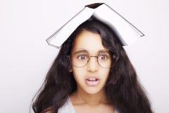 Entzückendes Mädchen, das mit Brillen und Buch auf dem Kopf studiert Lizenzfreies Stockbild