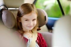 Entzückendes Mädchen, das sicher im Autositz sitzt lizenzfreie stockfotografie
