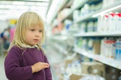 Entzückendes Mädchen in der Milchabteilung im Supermarkt Stockfotografie