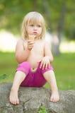 Entzückendes Mädchen essen die Eiscreme, die auf Stein sitzt Stockfoto