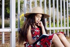 Entzückendes Mädchen im Kleider- und Hutlesebuch im Sommer parken Lizenzfreie Stockfotos