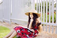 Entzückendes Mädchen im Kleider- und Hutlesebuch im Sommer parken Lizenzfreie Stockbilder