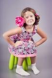 Entzückendes Mädchen im rosa Sitzen auf grünem Stuhl stockfotos