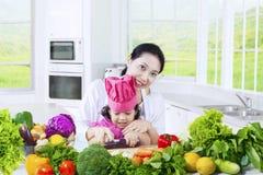 Entzückendes Mädchen und Mutter, die Gemüse kocht lizenzfreies stockfoto