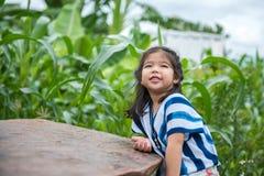 Entzückendes Mädchensitzen und -lächeln im Garten lizenzfreies stockbild