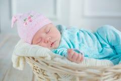 Entzückendes nettes Baby, das im weißen Korb auf Bretterboden schläft Stockfoto