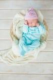 Entzückendes nettes Baby, das im weißen Korb auf Bretterboden schläft Lizenzfreies Stockfoto