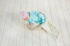 Entzückendes nettes Baby, das im weißen Korb auf Bretterboden schläft Stockbilder
