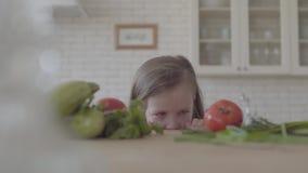 Entzückendes nettes kleines Mädchen des Porträts schaut von der Tabelle und versteckt das Schauen in der Kamera Frischgem?sezucch stock video footage
