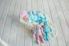 Entzückendes nettes süßes Baby, das im weißen Korb auf Bretterboden mit zwei Spielzeug tilda Kaninchen schläft Stockbild