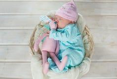 Entzückendes nettes süßes Baby, das im weißen Korb auf dem Bretterboden umarmt Spielzeug tilda Kaninchen schläft Stockbild