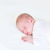 Entzückendes neugeborenes Baby, das auf einer weißen Decke schläft Stockfotos