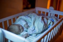 Entzückendes neugeborenes Baby, schlafend in der Krippe nachts lizenzfreie stockfotos