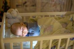 Entzückendes neugeborenes Baby, schlafend in der Krippe nachts stockbild