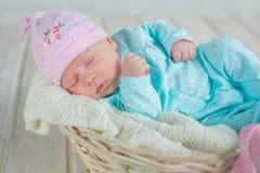 Entzückendes qute Baby, das im weißen Korb auf Bretterboden schläft Stockbild