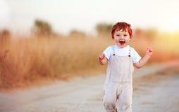Entzückendes Rothaarigebaby, das den Sommerweg laufen lässt lizenzfreie stockfotografie