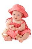 Entzückendes Schätzchen im rosafarbenen Kleid spielt mit Spielzeughäschen Lizenzfreies Stockbild