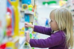 Entzückendes Schätzchen mit Spielwaren auf Regalen im Mall Stockfoto