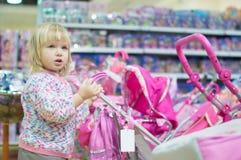 Entzückendes Schätzchen mit Spielzeugwagen im Mall Lizenzfreies Stockfoto
