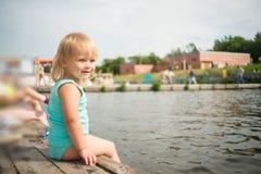 Entzückendes Schätzchen sitzen auf Pier nahe Wasser Lizenzfreies Stockfoto