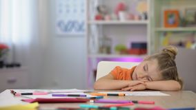 Entzückendes Schulmädchen, das auf Schreibtisch, Farbbleistiften und Papierauflage, Ausbildung schläft stock video footage
