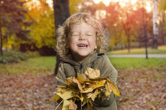 Entzückendes smileykind, das mit Blättern im Park spielt stockbild
