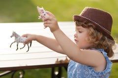 Entzückendes Spiel des kleinen Mädchens mit Tierspielwaren Stockfotos