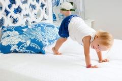 Entzückendes spielerisches Kleinkindmädchen im Schlafzimmer Lizenzfreie Stockfotografie