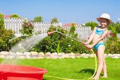 Entzückendes strömendes Wasser des kleinen Mädchens vom Schlauch und Stockfotografie