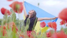 Entzückendes Tanzen der jungen Frau in einer Mohnblumenfeld-Holdingflagge von Ukraine in den Händen draußen Verbindung mit Natur stock footage