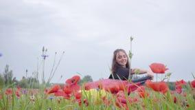 Entzückendes Tanzen des jungen Mädchens in einer Mohnblumenfeld-Holdingflagge von Deutschland in den Händen draußen Verbindung mi stock video