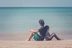 Entzückendes und Familien-Konzept: Frau und Kinder, die zurück zu Rückseite auf Sandstrand sitzen stockfotografie