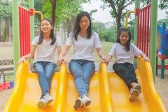 Entzückendes und Feiertags-Konzept: Frau und nette kleine Kinder, die lustig sich fühlen und Glück auf einem Dia am Spielplatz lizenzfreie stockfotos