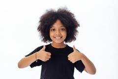 Entzückendes und nettes Afroamerikanerkind mit der Afrofrisur, die Daumen aufgibt stockfoto