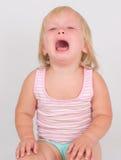 Entzückendes unzufriedenes Mädchen sitzen und schreien auf Weiß Lizenzfreie Stockfotografie