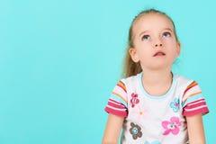 Entzückendes Vorschülermädchen tief in den Gedanken, oben schauend Konzentration, Entscheidung, Visionskonzept Lizenzfreies Stockbild