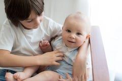 Entzückendes Vorschulkind, seinen Babybruder umarmend, wenn ch geschaukelt wird lizenzfreie stockfotos