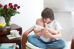 Entzückendes Vorschulkind, seinen Babybruder umarmend, wenn ch geschaukelt wird stockbild
