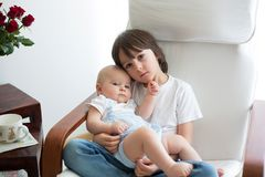 Entzückendes Vorschulkind, seinen Babybruder umarmend, wenn ch geschaukelt wird stockbilder