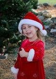 Entzückendes Weihnachtsmädchen in Sankt-Hut Stockfoto